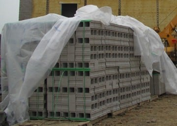 Store units and materials to produce mortar and grout off the ground and covered to keep them free from ice, snow, containments, and moisture intrusion.