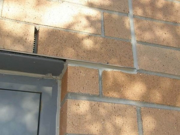 Figure7: Vertical movement joint properly located at the end of the beam bottom plate that supports the clay brick veneer at the door opening. Sealant properly installed under drip edge to prevent wind driven rain penetration.